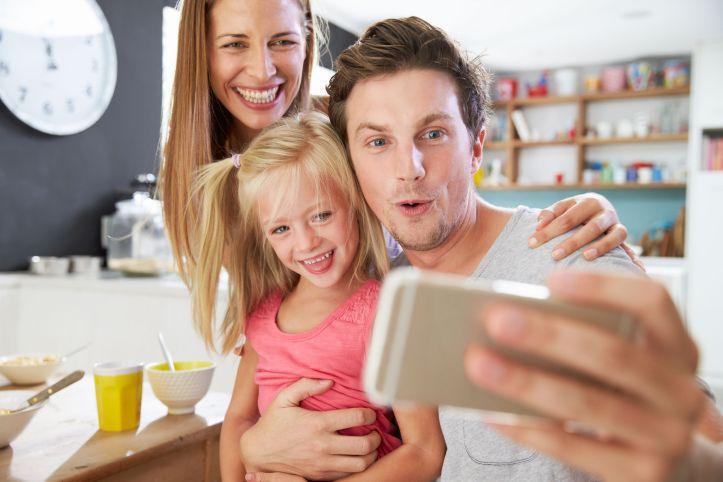 41461760 - family posing for selfie at breakfast table